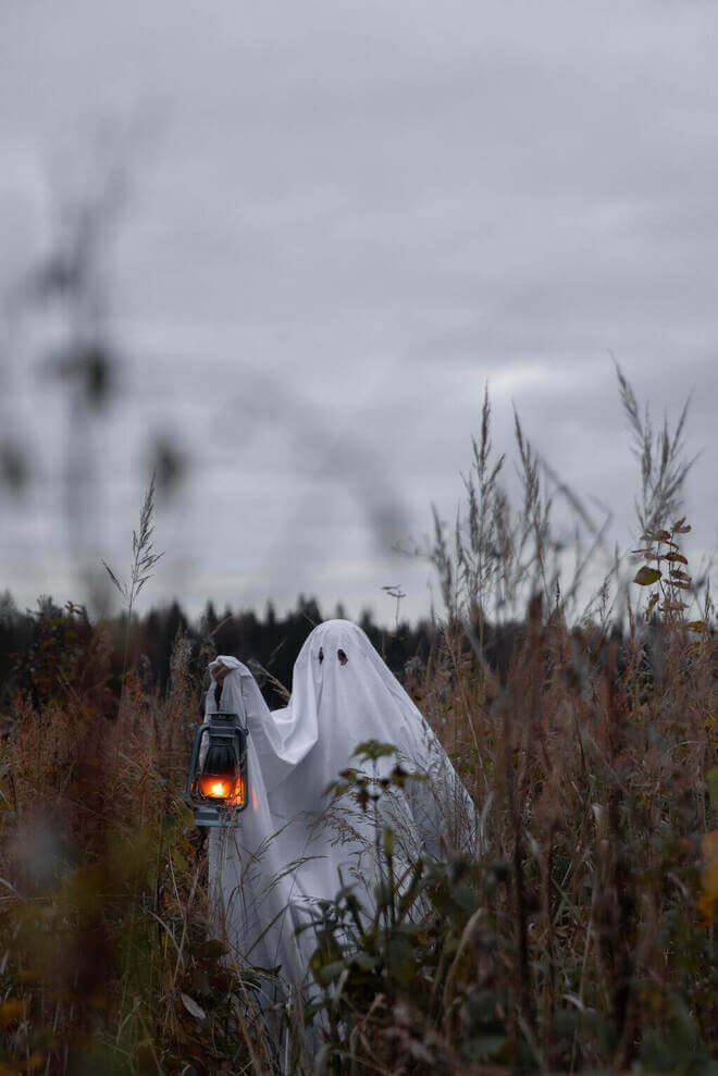 ghost in field with lantern